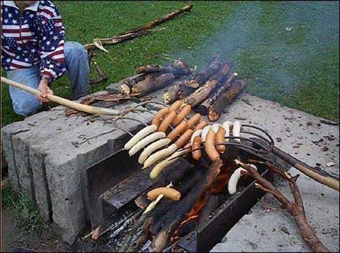 Grilling sausages with pitchforks